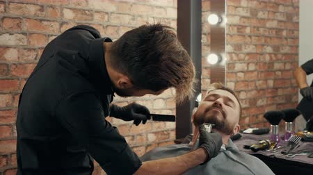 Closeup shot of focused barber trimming beard of client. Concentrated hairdresser grooming handsome male client in barbershop. Male beauty concept Stock Footage