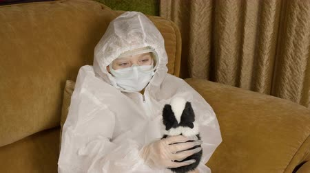 Sick teenager girl in protective costume playing with hamster on home sofa while quarantine. Diseased girl infected coronavirus in protective clothes sitting on couch. Coronavirus MERS concept