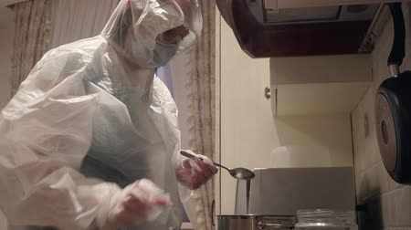 Infected woman in protective suit cooking on home kitchen. Woman in white costume for corona virus protection preparing food in home. People live during coronavirus epidemic in China