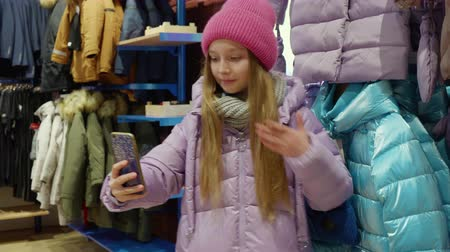 seçme : Blogger girl shooting online video to mobile phone new clothes in fashion boutique. Young teenager girl posing for selfie photo clothes store at shopping. Overview stylish clothes