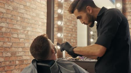 Barber shaving beard with electric razor to hipster man back view. Shaving bearded man with electric machine in barber shop. Male barber trimming bearded beard with shaver Stock Footage