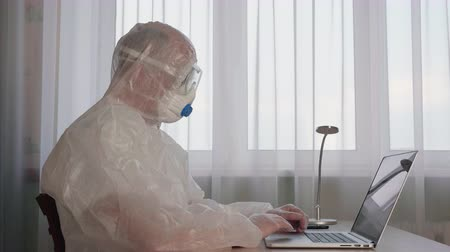 Office man in protective costume working on laptop while epidemic quarantine. Man in white protective suit using notebook in office while coronavirus epidemy. Prevention infection during an outbreak