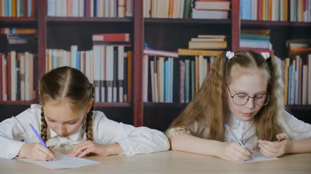 biblioteca : Worried small girl cribbing from paper during exam. Little schoolgirls cheating during school test. Cheating on exam concept