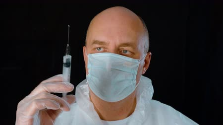 Front view of doctor releasing excess air from syringe. Man wearing protective mask preparing injection. Medical injection concept