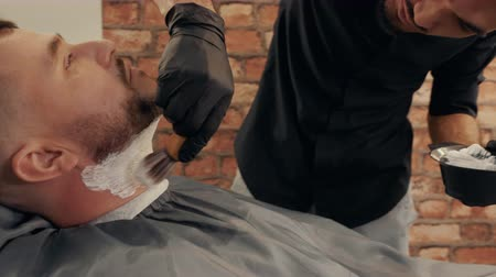 Concentrated barber applying shaving foam on man beard. Focused stylist working with client. Male beauty concept