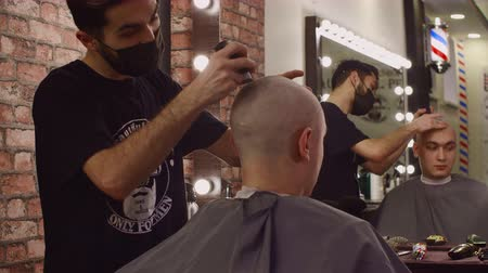 Professional hairstylist shaving bald head of client. Concentrated hairdresser in facial mask serving male client in barbershop. Male beauty concept