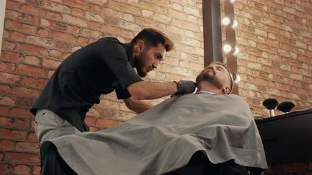 Low angle shot of focused barber cutting beard to client. Concentrated hairdresser grooming handsome male client in barbershop. Male beauty concept