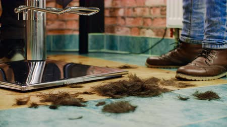 atualizar : Cutted hair falling down on floor at barber shop. Cropped partial view of hairdresser working with client. Haircut update concept. Slow motion Vídeos