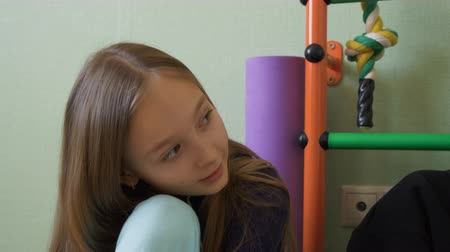 Thoughtful young girl sitting in playroom. Pensive preadolescent child talking with someone. Thinking concept