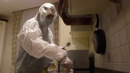 bio hazardous : Sick woman cooking on home kitchen in protective suit to prevent infection. Woman in protective costume preparing food in home for coronavirus protection. Hazard infection corona virus