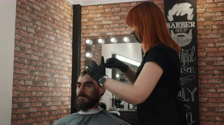 kapster : Happy bearded man talking with barber while hair cut in male salon. Hairstylist red hair woman cutting hair for hipster man in barber shop. Handsome man getting haircut in barbershop Stockvideo