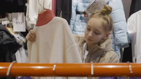 seçme : Young teenager girl looking jacket in clothes showroom at shopping. Young woman choosing clothes in fashion boutique. Girl teenager shopping in clothes store Stok Video