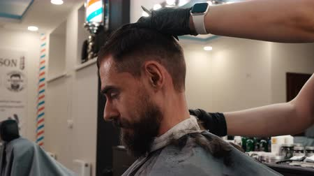 kapster : Bearded man receiving neck shave with electrical machine in barber salon. Haircutter shaving male neck with electrical razor in male salon. Male hairstyle with trimmer on barbershop