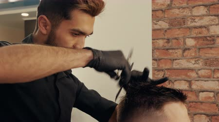 prádelník : Hairdresser cutting hair with barber scissors and comb in male salon. Close up male hairdressing in barber shop. Stylish male haircut for hipster man in salon