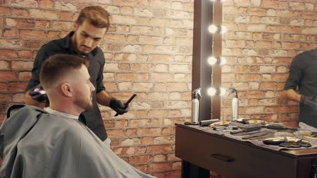 kapster : Barber sweeping stubble from male face after shaving and hair cutting in salon. Male barber serving bearded client in barbershop. Male hair and beard care in salon Stockvideo