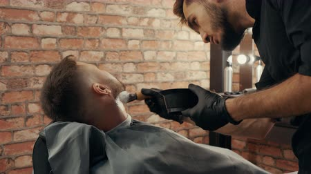 shaving foam : Barber applying foam on male face for wet beard shaving in male salon. Stylist preparing client to wet shaving with straight razor in barber shop. Male skin and beard care Stock Footage