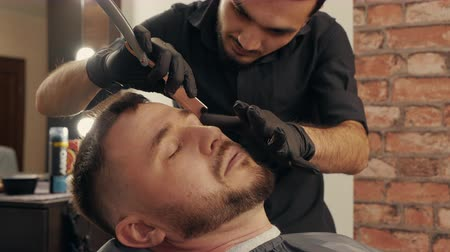 tıraş : Close up barber shaving with straight razor to bearded man in male salon. Shaving hair on face with straight razor in barbershop. Shave beard in male hairdressing salon Stok Video