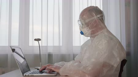 bactérias : Bioengineer in white protective suit using laptop in chemical laboratory. Office worker in white protective suit using notebook in while epidemic quarantine. MERS Chinese infection concept