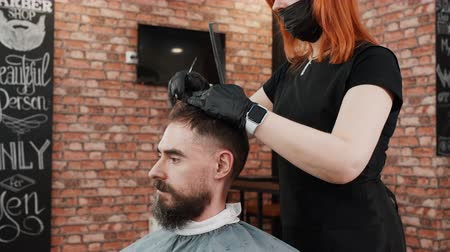kapster : Female hairdresser in facial mask cutting hair of client. Professional hairstylist working with man at workplace. Haircut concept