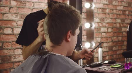 kapster : Professional hairstylist shaving head of client. Hairdresser in facial mask serving male client in barbershop. Male beauty concept Stockvideo
