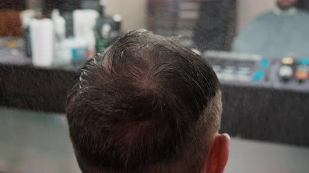 kapster : Close up shot of spraying water on head of client. Cropped shot of hairdresser working with man at workplace. Haircut concept Stockvideo