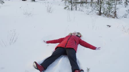 chapéu : Happy teenage girl making snow angel in winter forest. High angle view of cute teenage girl in red jacket lying in snow and having fun at wintertime