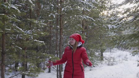 leaping : Cute happy girl playing with snow throw in winter forest. Beautiful cheerful teenage girl walking between snow-covered pine trees in forest at wintertime
