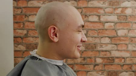 прическа : Bald man with shaved head sitting in barber chair in male salon. Profile view bald man after shave talking in barbershop. Portrait young man in hairdressing salon Стоковые видеозаписи