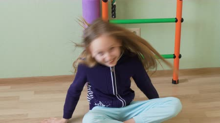 sallama : Cheerful girl teenager dancing sitting on floor in school gym. Happy girl teenager shaking long hair sitting on floor in gym room Stok Video