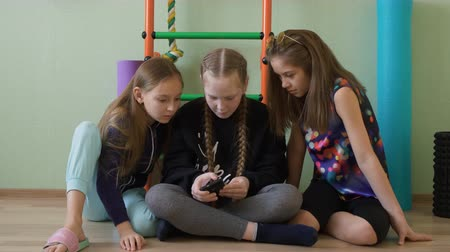 descanso : Three school girl using mobile phone in gym class at break. Teenager girl friends looking smartphone sitting on floor in school gym