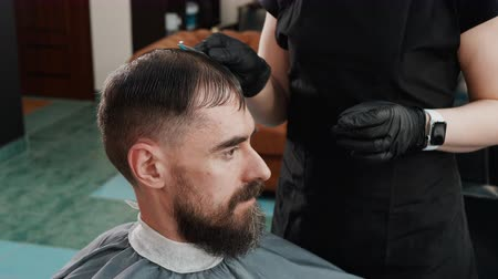 opvangen : Hairdresser combing wet hair bearded man before haircut. Barber combing male hair for hairdressing in male salon. Bearded man receiving hair cutting in barbershop Stockvideo
