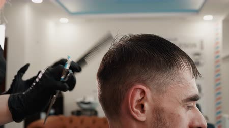 grzebień : Hairstylist combing wet male hair before cutting in male salon. Bearded man getting stylish haircut in barbershop. Stylist using comb for haircut in barber salon Wideo