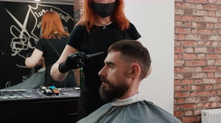 prádelník : Bearded man getting haircut in chair in barbershop. Woman cutting hair with scissors of hipster man in barber salon. Portrait hipster man while hairdressing in male salon