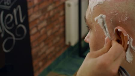 shaving foam : Close up shaving head of bald man with straight razor in barber salon. Barber shaving head by dangerous razor and soap foam in male salon. Male hair and head skin care