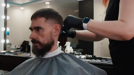 beard trim : Female hairdresser trimming hair of client with scissors. Professional hairstylist working with man at workplace. Haircut concept