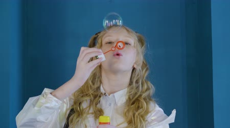 Cute girl blowing soap bubbles. Slow motion view of curly blonde girl inflating colorful soap bubbles. Leisure concept 動画素材