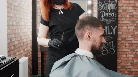 поворотный : Hairdresser in facial mask cutting hair of client with scissors. Professional female hairstylist working with man at workplace. Haircut concept Стоковые видеозаписи