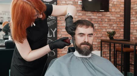 grzebień : Barber cutting beard with electrical shaver to hipster man in male salon. Bearded man getting shaving beard with trimmer in barbershop. Male hair and beard care in barber salon Wideo