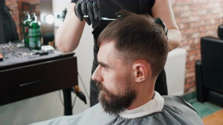 opvangen : Hairdresser combing and cutting with scissors male hair in barbershop. Bearded man receiving hair cut with comb and scissors in barber salon. Male beauty industry
