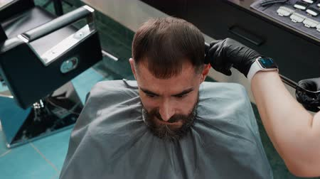grzebień : Hairdresser hands cutting male hair with scissors and comb in barbershop. Bearded man receiving haircut with scissors in male salon. Top view stylish hairdo in male salon.