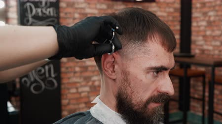 mestre : Hairstylist quickly cutting male hair by scissors in barber salon. Barber cutting male hair with professional scissors close up. Handsome man getting haircut in barbershop Vídeos