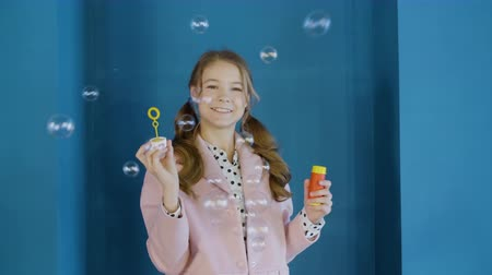 pigtailler : Cheerful teen girl blowing soap bubbles in studio on blue wall background. Smiling schoolgirl with two curly hair tail blowing bubbles soap front camera