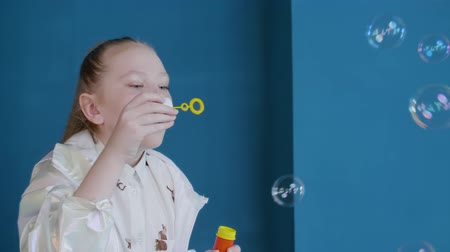 косички : Cute teenager girl blowing soap bubbles on blue wall background in studio. Playful freckled schoolgirl blowing up bubbles soap inside blue studio