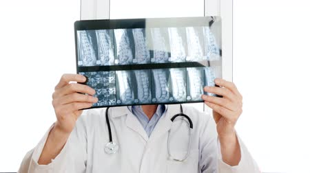 csontok : Male doctor looking x-ray of backbones and negatively shaking head. Portrait surgeon watching spine bones and saying no. Medical worker in white medical gown with phonendoscope holding x-ray Stock mozgókép