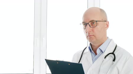clínico : Portrait male doctor in white coat writing prescription check list on clip board. Practitioner writing medical examination at medical clinic. Medical worker in medical gown stethoscope in hospital