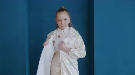 vybírání : Teenager girl model posing in white jacket on blue wall background. Fashion teenager girl posing in stylish white coat on podium in studio