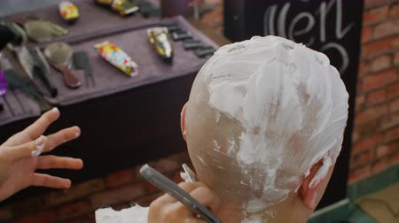 shaving foam : Process shaving bald man with straight razor and soap foam in barbershop. Close up shaving head by straight razor and foam in male salon. Male hair and head skin care Stock Footage