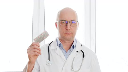 healthy office : Doctor in white coat showing tablet blister on white window background medical office. Portrait pharmacist in medical gown holding in hands drug pills in pharmacy from pocket Stock Footage