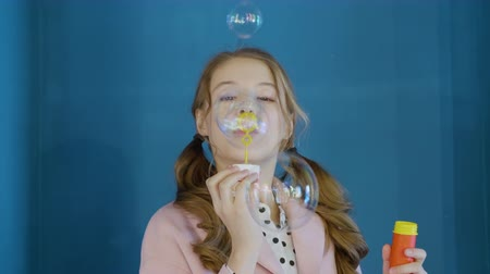 dětinský : Adorable teenager girl blowing soap bubbles and smiling on blue wall background. Beautiful girl with curly hair tails blowing bubbles soap in blue studio Dostupné videozáznamy