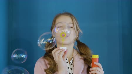 pigtail : Happy girl teenager blowing soap bubbles front camera in blue studio. Portrait young girl with two pigtails blowing bubbles soap on blue wall background Stock Footage